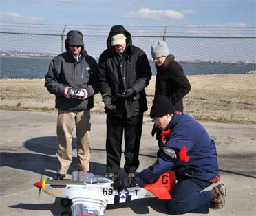 NRL researchers (l to r) Dr. Jeffrey Baldwin, Dr. Dennis Hardy, Dr. Heather Willauer, and Dr. David Drab (crouched), successfully demonstrate a novel liquid hydrocarbon fuel to power the aircraft's unmodified two-stroke internal combustion engine.